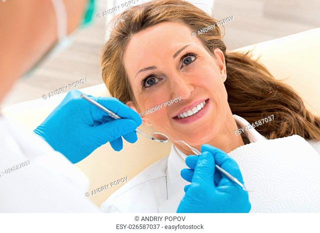 Happy Mature Woman Having Dental Check-up In Clinic