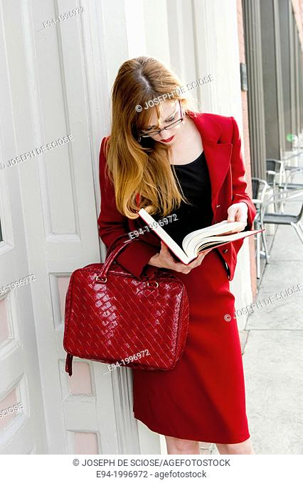 31 year old red headed woman in a business suit in an urban environment holding a law book