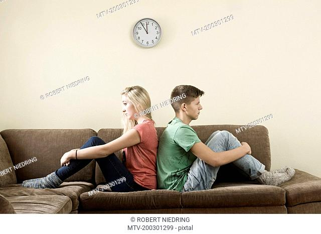 Serious looking teenage couple leaning back to back on couch