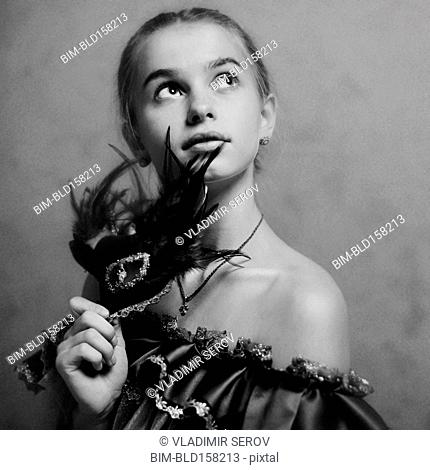 Caucasian girl holding feather mask