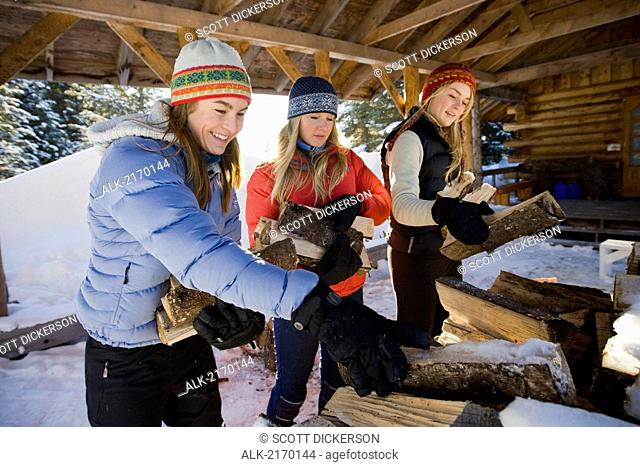 Three Young Women Collect And Pile Chopped Wood Near Homer, Alaska During Winter
