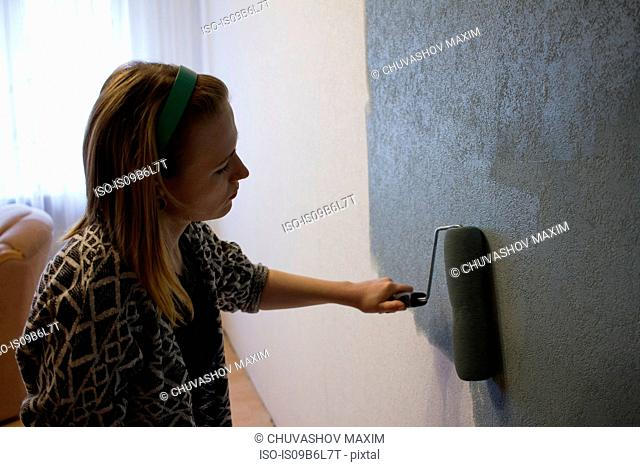 Young woman applying grey paint with roller to interior wall at home