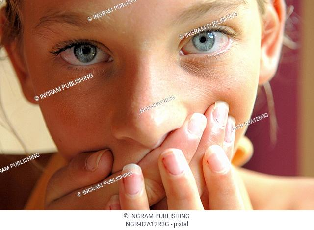 Close-up of a girl covering her mouth with her hands