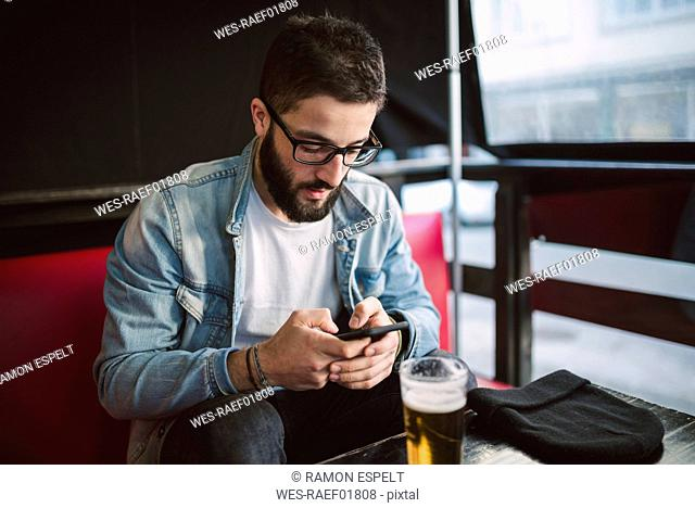 Young man text messaging in a pub
