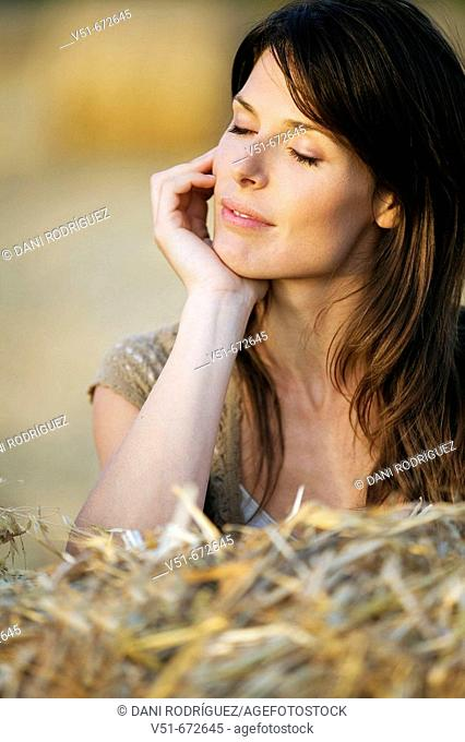 Woman outdoors with eyes closed feeling good