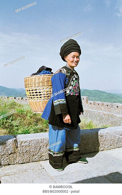 Portrait of a mature woman with a wicker basket, The miao minority women on the southern Great Wall, Fenghuang, Xiangxi Prefecture, Hunan Province