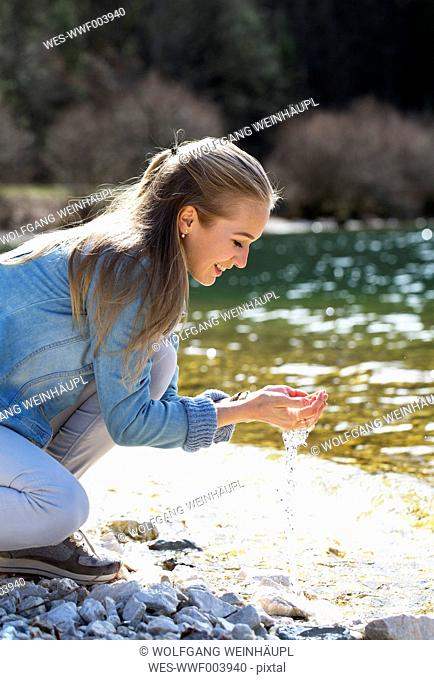 Smiling teenage girl crouching at lakeshore holding water in her hands