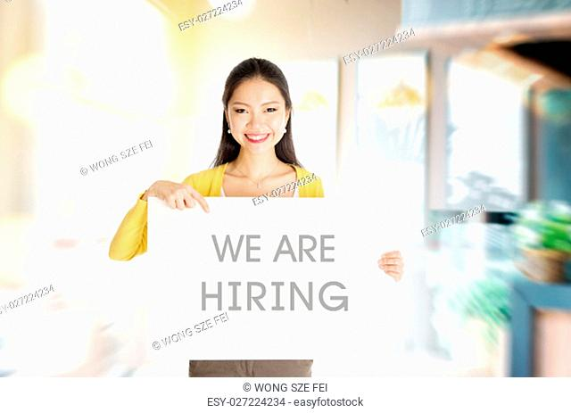 "Young Asian woman hand holding """"we are hiring"""" board sign in restaurant or cafe"