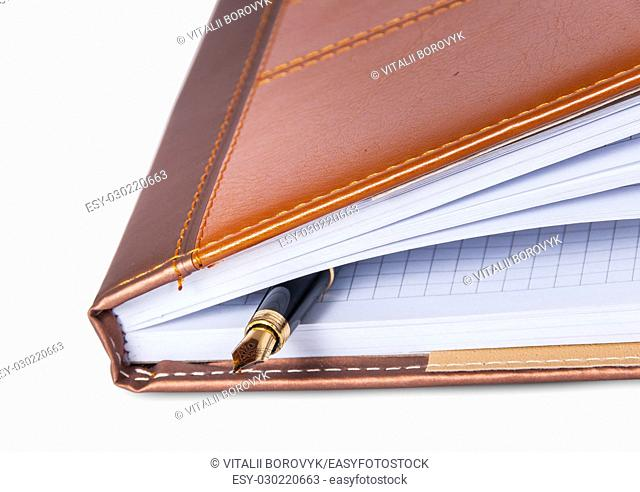 Closeup fountain pen located inside the notebook isolated on white background