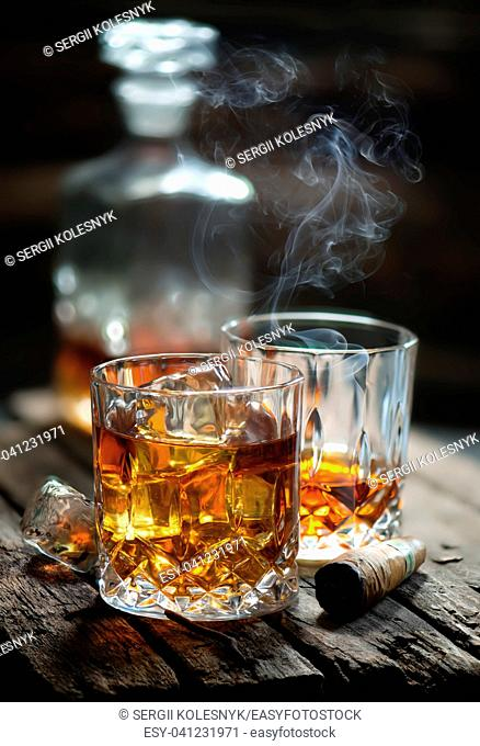 Cigar and glass with whiskey with ice cubes