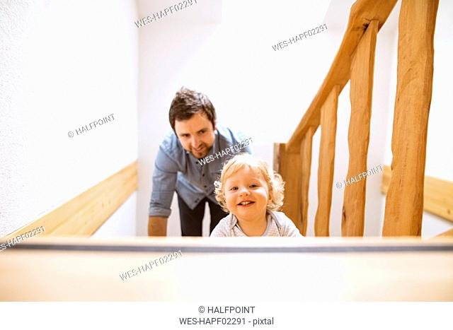 Father with little boy on wooden stairs at home