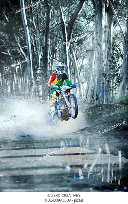 Young male motocross racer riding through dirt track puddle in forest