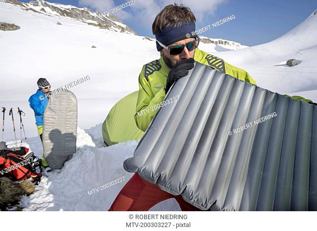 Two men blowing into air mattresses for camping, Tyrol, Austria