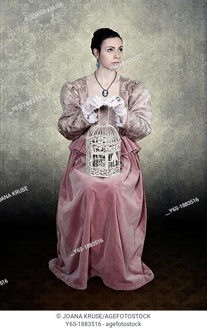 a woman in a victorian dress is sitting on a chair, a birdcage on her lap