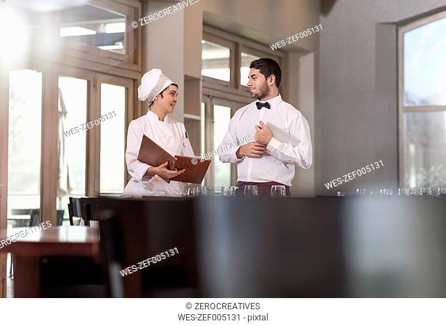 Chef and waiter in restaurant discussing menue