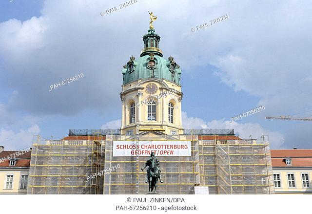 A banner that reads 'Charlottenburg Palace open' pictured on the main building that is surrounded by scaffolding at Charlottenburg Palace in Berlin, Germany