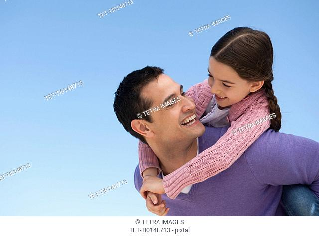 Father giving piggyback ride to daughter 8-9