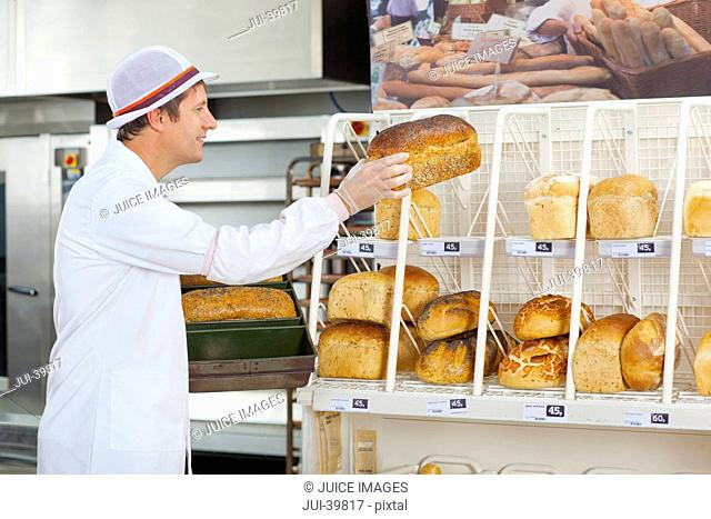 Baker With Loaves In Bread Department Of Supermarket