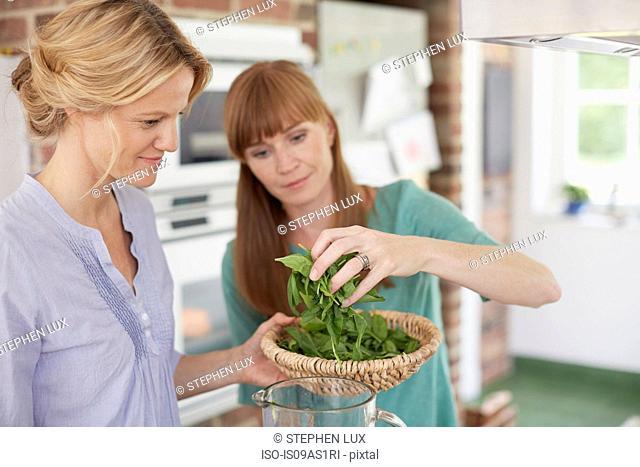 Women preparing green vegan smoothie in kitchen