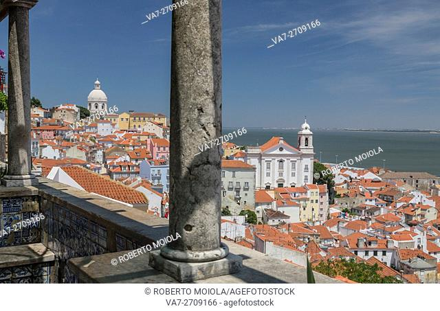 The columns on a terrace frame terracotta roofs and the ancient dome at Miradouro Alfama Viewpoint of Lisbon Portugal Europe