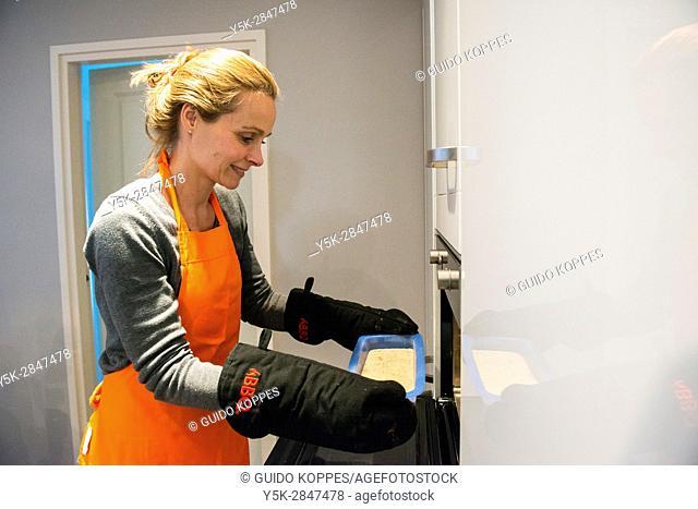 Kaatsheuvel, Netherlands. Mid adult caucasian female removing freshly baked ccake form heated her kitchen oven