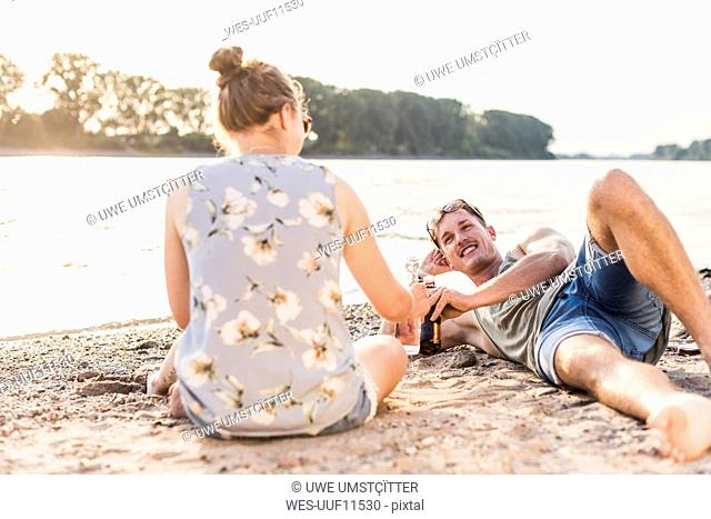 Young couple relaxing at the riverbank
