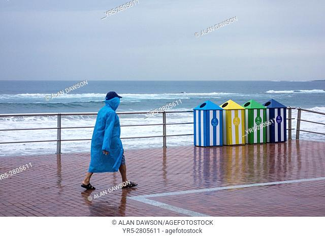 Man walking in the rain near Las Canteras beach in Las Palmas, Gran Canaria, Canary Islands, Spain