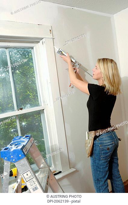 Woman Putting Caulking Around Window