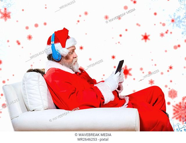 Santa listening to headphones and using digital tablet while sitting on a couch