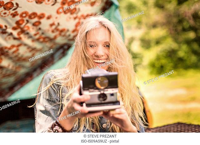 Portrait of young woman photographing with instant camera whilst camping