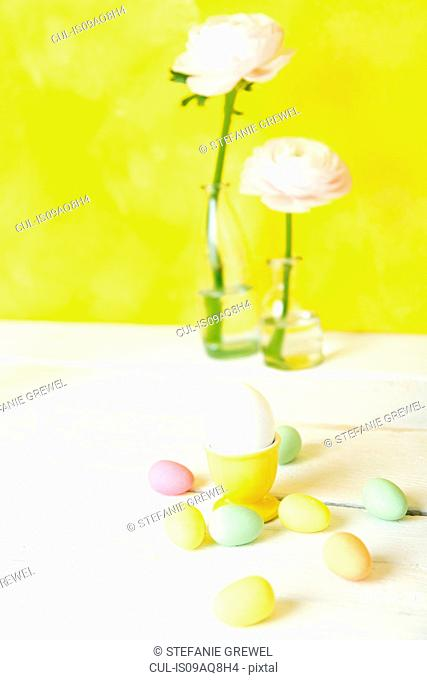 Still life of cut flowers in bottles and confectionery Easter eggs