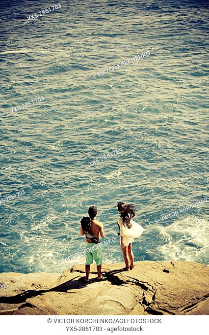 Young couple standing on the edge of a rock by the ocean near Honolulu, Hawaii
