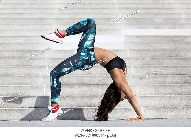 Young woman doing gymnastics at outdoor stairs