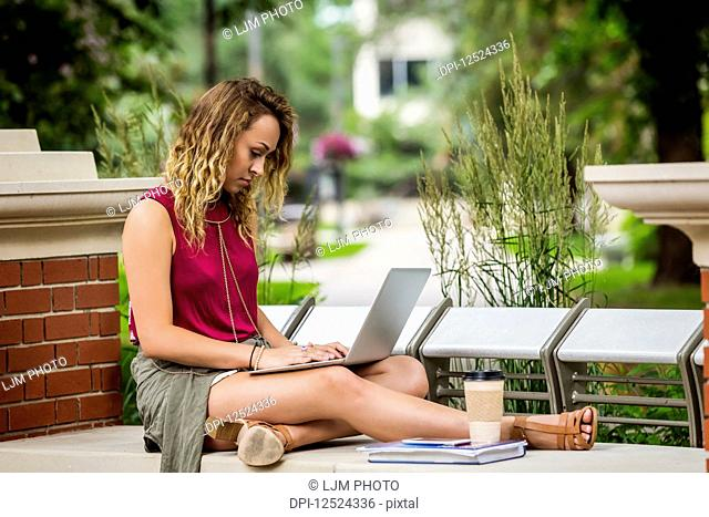 A beautiful young female university student sits working on her laptop on a park bench outside in the campus; Edmonton, Alberta, Canada
