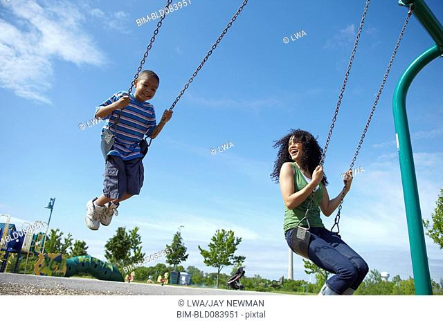 Black mother and son swinging on swing set