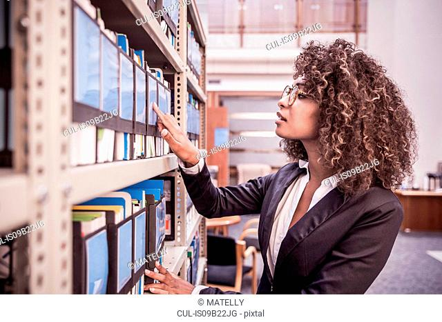Young businesswoman searching office shelves