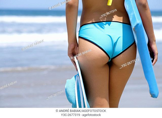 Close up back side section view of young woman in bikini with summer hat and boogie board