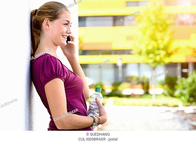 Young woman talking on smartphone in park