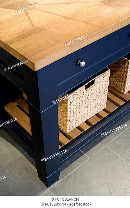 Close-up of storage basket on low shelf of island kitchen unit
