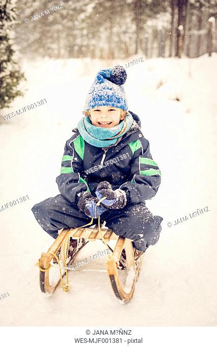 Germany, Bavaria, Berchtesgadener Land, happy boy on sledge