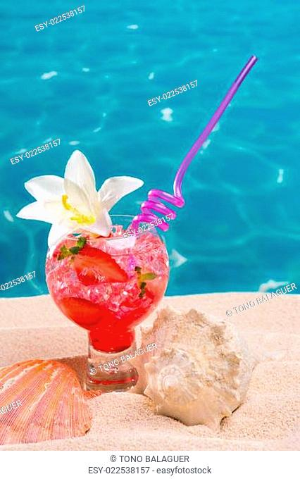 Strawberry cocktail on beach sand with seashells