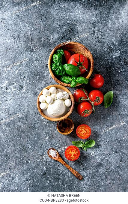 Ingredients for italian caprese salad. Mozzarella balls, buffalo, tomatoes, basil leaves, olive oil with vinegar, salt in olive wood bowls over gray texture...