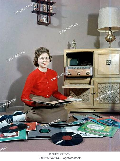 Young woman sitting on floor and choosing vinyl records