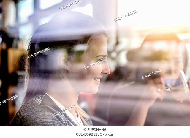 Two female students having coffee in cafe window seat