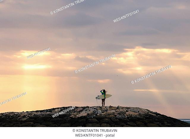 Indonesia, Bali, young woman with surf board in the evening
