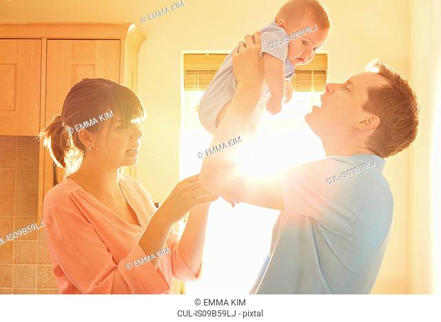 Mature man with wife holding up baby son in sunlit kitchen