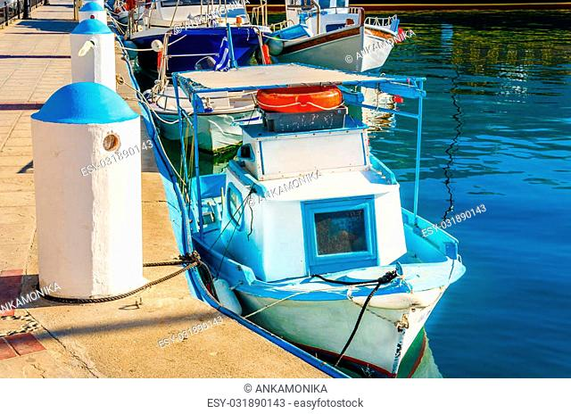 Very samll wooden boat painted in Greek blue and white colors in port