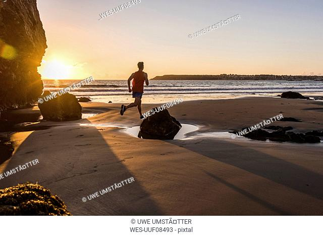 France, Crozon peninsula, jogger on the beach at sunset