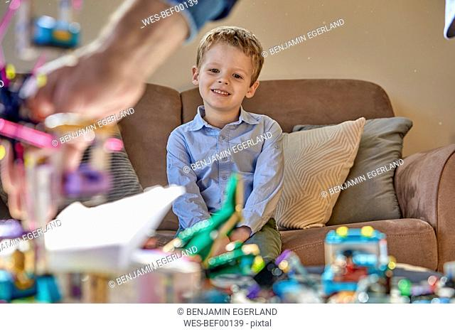 Smiling boy sitting on couch looking at toys on table