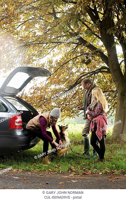 Family and dog preparing for walk from car boot, Norfolk, UK